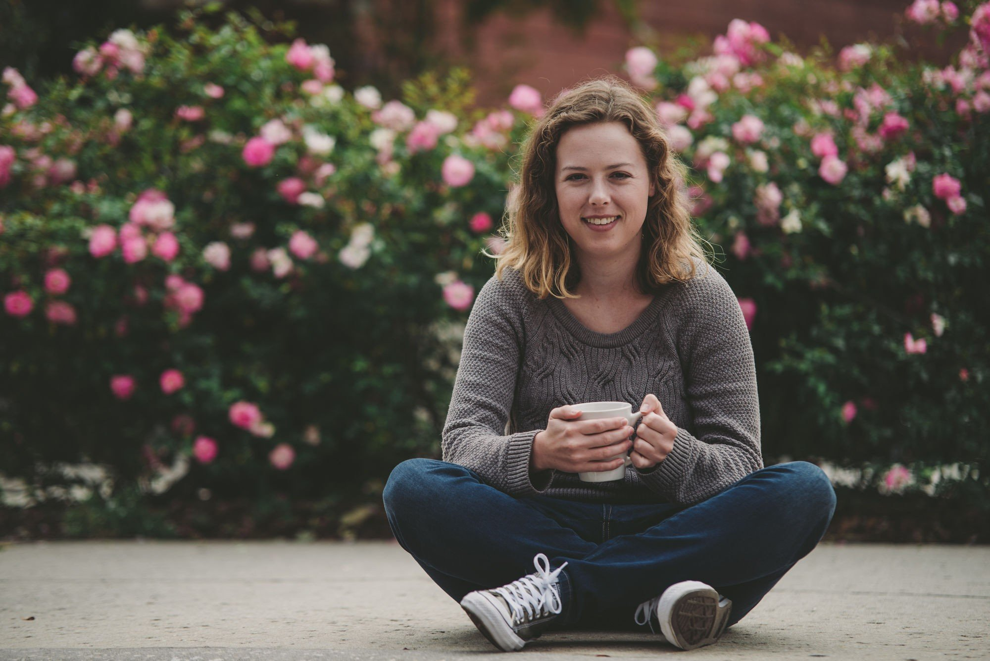 A photograph of Elizabeth Geren conversationally sitting down with a cup of coffee.